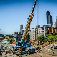 full color thumbnail of blocked off road in Seattle with GMK 5220 crane with crews attaching a section of a vault to lift
