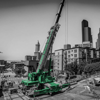 black and white and green thumbnail of blocked off road in Seattle with GMK 5220 crane with crews attaching a section of a vault to lift