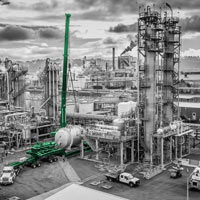 black and white and green thumbnail of perspective from sky of omega morgan crane attached to lift cylindrical vessel from trailer at chemical plant