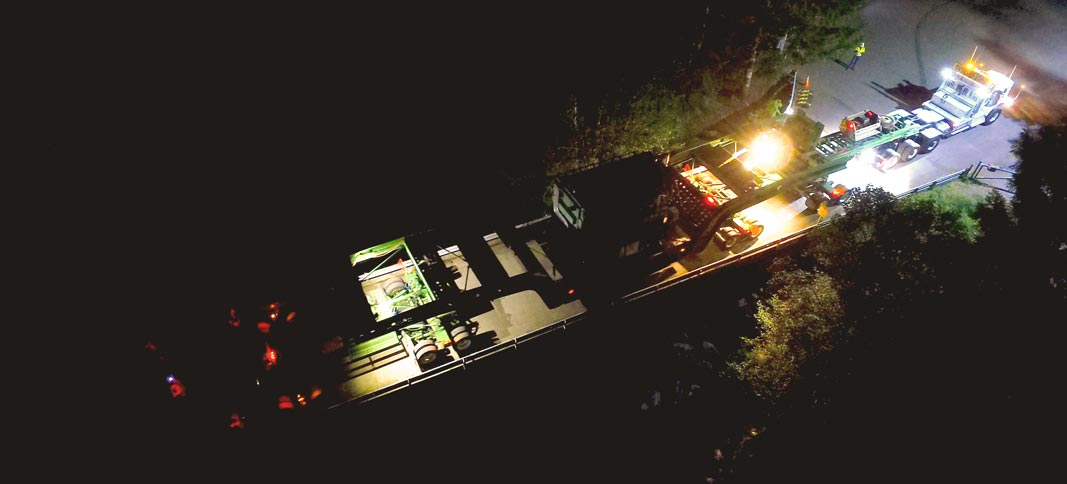 view from the sky of Omega Morgan transporting a 158,000 pound transformer over a bridge at night