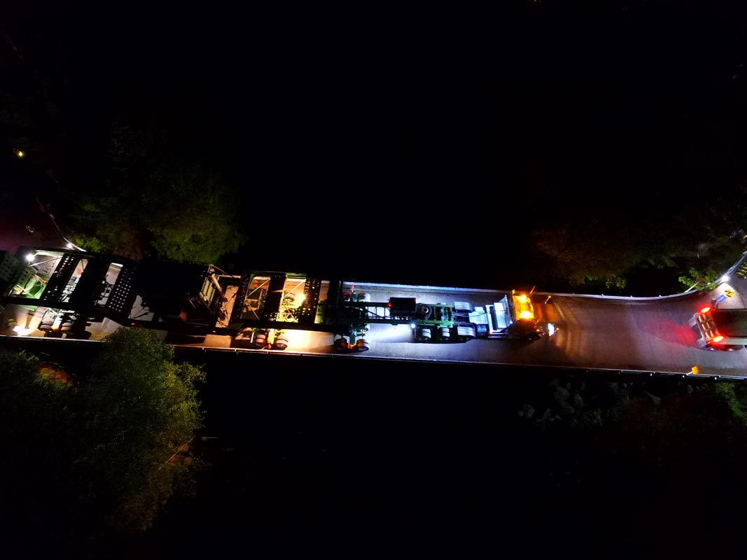 view from the sky of Omega Morgan's specialized transportation team transporting a 158,000 pound transformer over a bridge at night