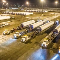 selected video thumbnail button of Omega Morgan specialized transportation semi trucks lined up with wind turbine segments in tow
