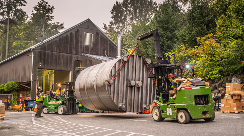 Omega Morgan machinery moving crew moving large equipment at Woodinville Whiskey distillery in Woodinville, Washington