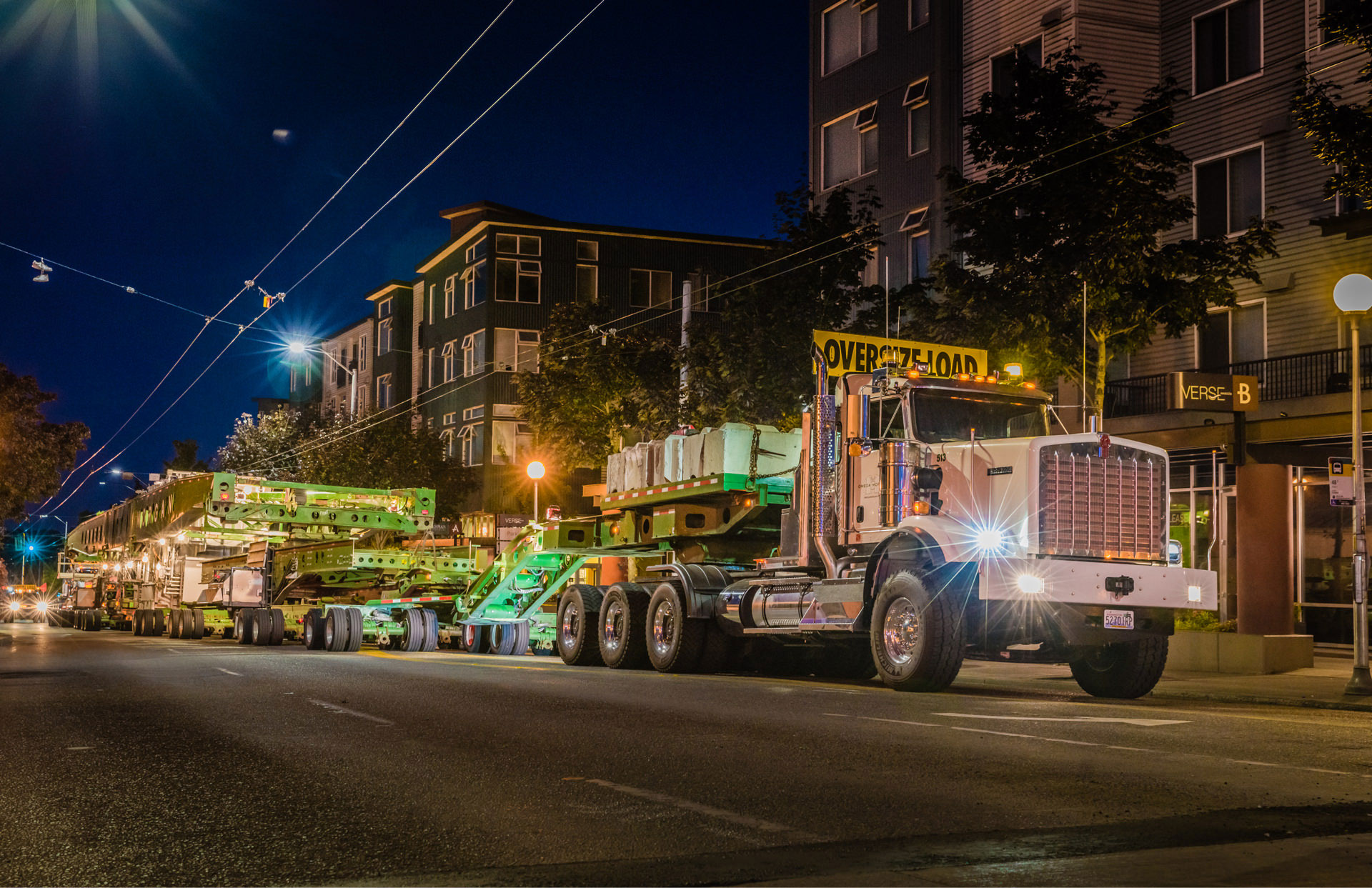 specialized transportation truck and trailer driving in city at night