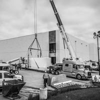 deselected thumbnail button of vehicles and crew assemble at the JE Dunn data center in Hillsboro, Oregon ready to lift a power skid into the building
