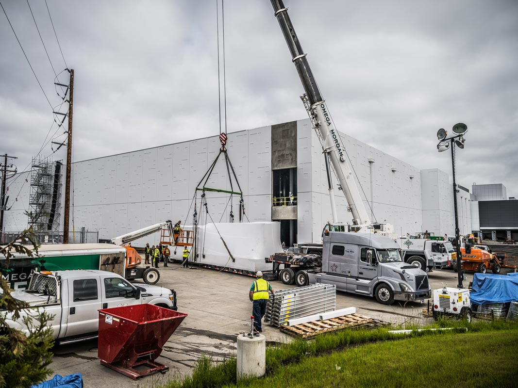 vehicles and crew assemble at the JE Dunn data center in Hillsboro, Oregon ready to lift a power skid into the building