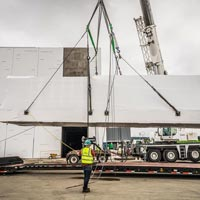 selected thumbnail button of Omega Morgan Crane lifting a power skid off of a trailer in front of the JE Dunn data center in Hillsboro, Oregon