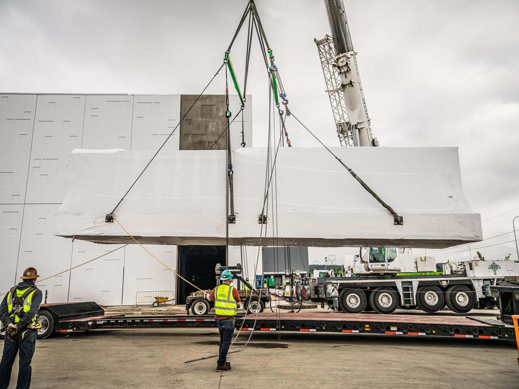 Omega Morgan Crane lifting a power skid off of a trailer in front of the JE Dunn data center in Hillsboro, Oregon