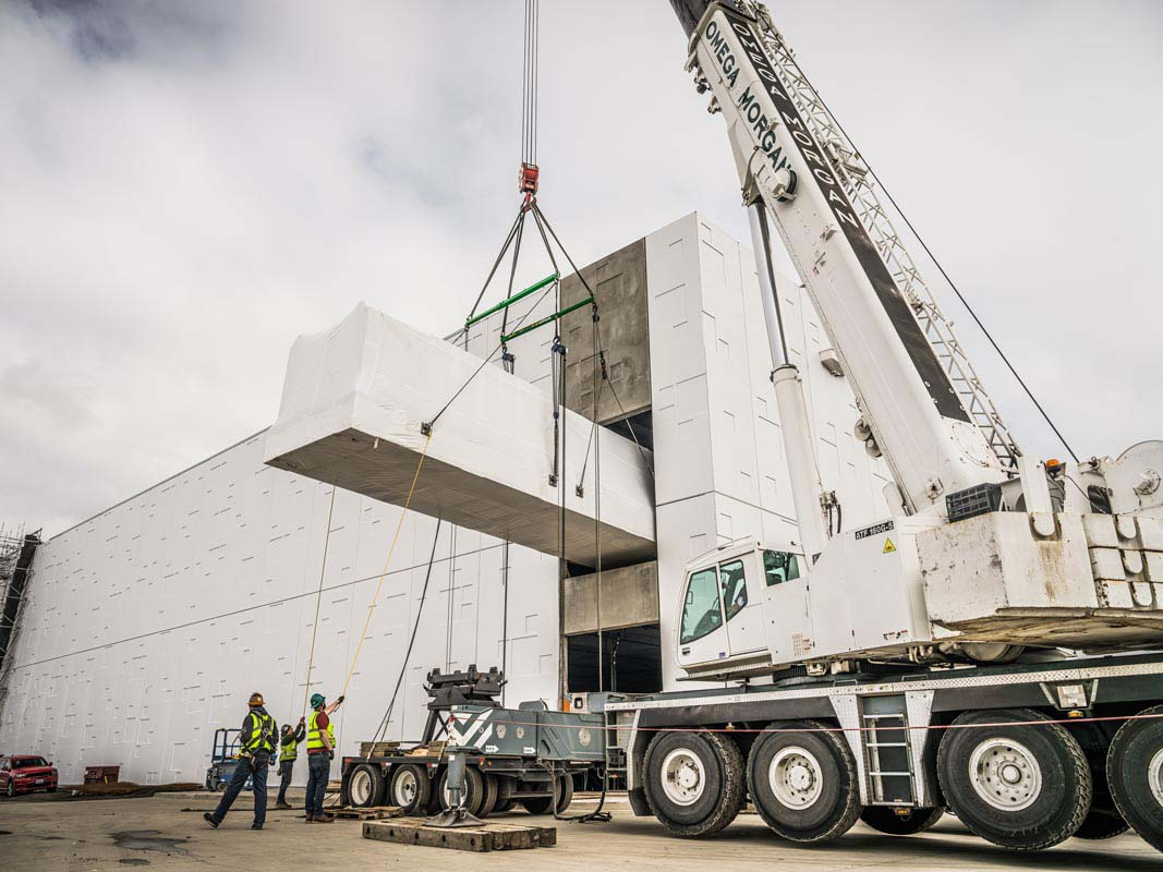 View from behind an Omega Morgan crane lifting a power skid into the JE Dunn data center building