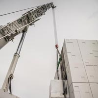 selected thumbnail button of the tip of an Omega Morgan crane as it lifts a power skid into the JE Dunn Data Center in Hillsboro, Oregon