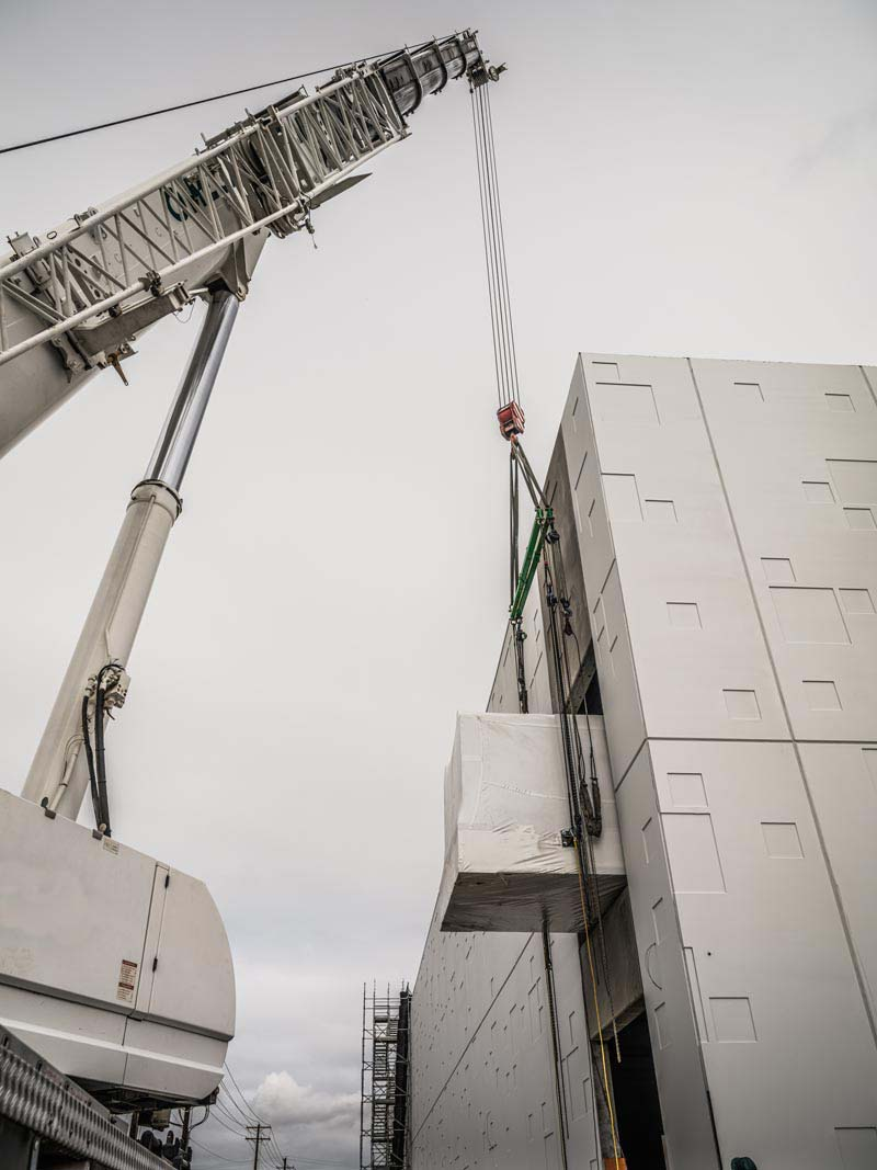 the tip of an Omega Morgan crane as it lifts a power skid into the JE Dunn Data Center in Hillsboro, Oregon
