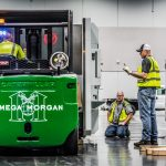 Omega Morgan Machinery moving crew at the Oregon Convention center, moving a piece of machinery into place. Two men observe while one operates the caterpillar forklift.