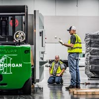 selected thumbnail button of Omega Morgan Machinery moving crew at the Oregon Convention center, moving a piece of machinery into place. Two men observe while one operates the caterpillar forklift.