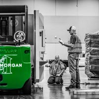 deselected thumbnail button of Omega Morgan Machinery moving crew at the Oregon Convention center, moving a piece of machinery into place. Two men observe while one operates the caterpillar forklift.