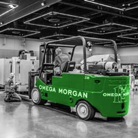 deselected thumbnail button of two Omega Morgan Machinery Moving crews working side by side to simultaneously set two pieces of machinery at the Northwest Machine Tool Expo at the Oregon Convention Center in Portland, Oregon