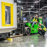 selected thumbnail button of two Omega Morgan machinery moving teammembers with one on a forklift precisely moving a large piece of machinery into place at the Oregon Convention Center