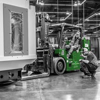 deselected thumbnail button of two Omega Morgan machinery moving teammembers with one on a forklift precisely moving a large piece of machinery into place at the Oregon Convention Center
