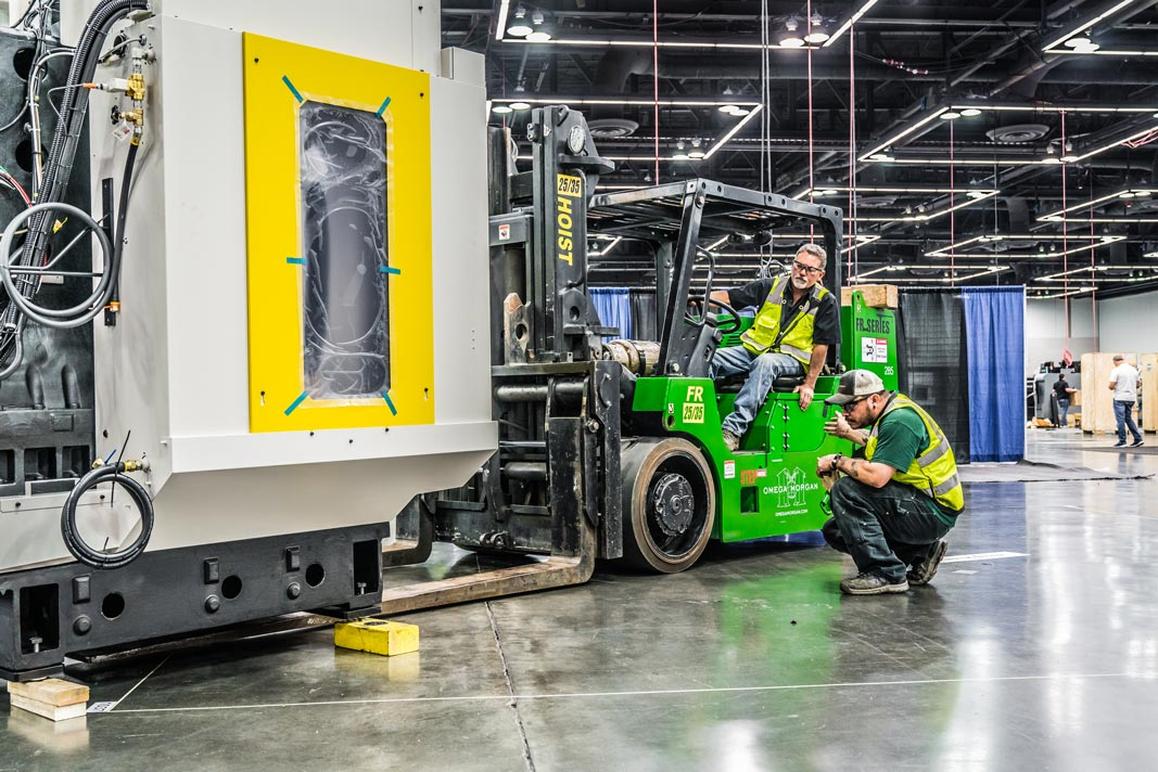 two Omega Morgan machinery moving teammembers with one on a forklift precisely moving a large piece of machinery into place at the Oregon Convention Center in Portland, Oregon