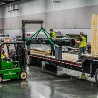 selected thumbnail button of Omega Morgan machinery moving crew in the Oregon Convention center carefully picking a long piece of machinery off of a truckbed for the Northwest Machinery Tool Expo