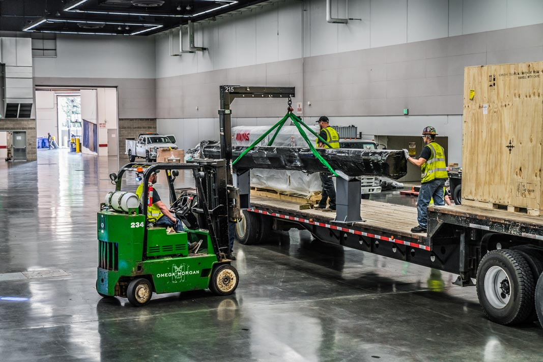 Omega Morgan machinery moving crew in the Oregon Convention center carefully picking a long piece of machinery off of a truckbed for the Northwest Machinery Tool Expo