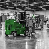 deselected thumbnail button of two Omega Morgan machinery moving crews lined up bringing machinery pieces into the booth areas for the upcoming Northwest Machine Tool Expo in the Oregon Convention Center