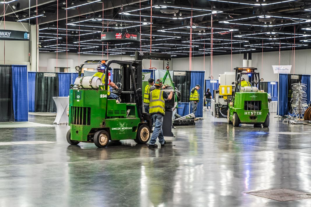 two Omega Morgan machinery moving crews lined up bringing machinery pieces into the booth areas for the upcoming Northwest Machine Tool Expo in the Oregon Convention Center