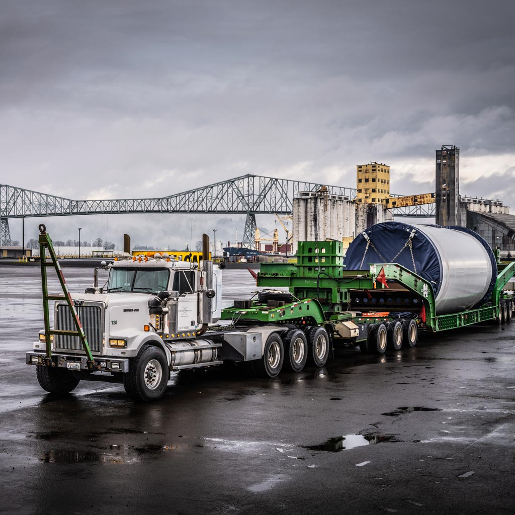 Omega Morgan specialized transportation tractor pulling a schnabel trailer holding a wind turbine section in front of the Longview bridge in Longview, Washington