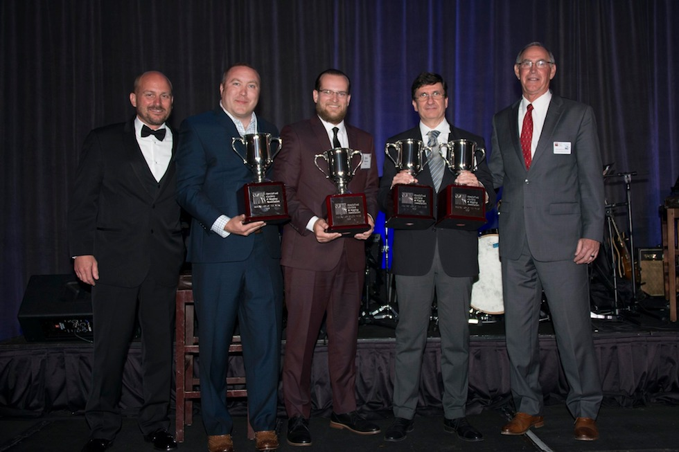 Omega Morgan's Erik Zander stands holding a trophy on stage along with the other two winners of the 2019 Specialized Carriers and Rigging Awards Hauling Job of the Year winners