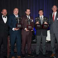 selected thumbnail button of Omega Morgan's Erik Zander stands holding a trophy on stage along with the other two winners of the 2019 Specialized Carriers and Rigging Awards Hauling Job of the Year winners