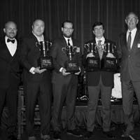 deselected thumbnail button of Omega Morgan's Erik Zander stands holding a trophy on stage along with the other two winners of the 2019 Specialized Carriers and Rigging Awards Hauling Job of the Year winners