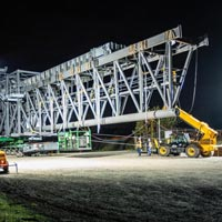 selected thumbnail button of Omega Morgan Specialized Transportation crews preparing a large ship loader for transport in Vancouver, Washington at night