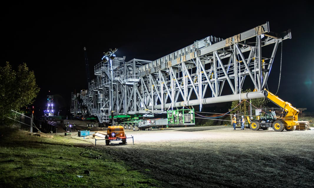 Omega Morgan Specialized Transportation crews preparing a large ship loader for transport in Vancouver, Washington at night
