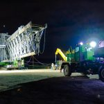 a nighttime scene of Omega Morgan specialized transportation crews moving a ship loader on a 6 line KMAG SPMT