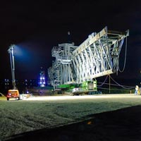 selected thumbnail button of a nighttime scene of Omega Morgan specialized transportation crews moving a ship loader on a 6 line KMAG SPMT
