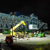 selected thumbnail button of a 530,000 pound ship loader being prepared for transport at night under bright spotlights with dollies, an SPMT and a prime mover