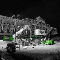 deselected thumbnail button of a 530,000 pound ship loader being prepared for transport at night under bright spotlights with dollies, an SPMT and a prime mover