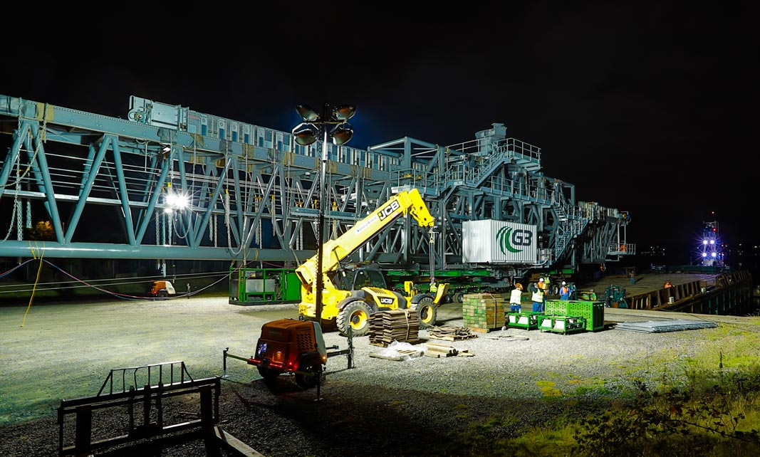 a 530,000 pound ship loader being prepared for transport at night under bright spotlights with dollies, an SPMT and a prime mover