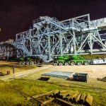 a 530,000 pound ship loader on top of a green KMAG 6-line SPMT at night