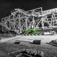 deselected thumbnail button of a 530,000 pound ship loader on top of a green KMAG 6-line SPMT at night