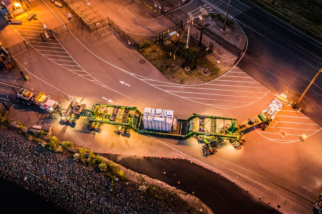 a view from overhead of a shunt reactor being carried by Omega Morgan specialized transportation setup at night