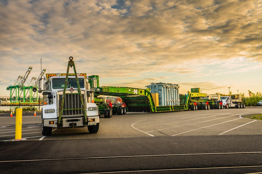 2015 Kenworth C500 truck parked on pavement with a 150-ton trailer carrying a shunt reactor in front of a cloudy sky
