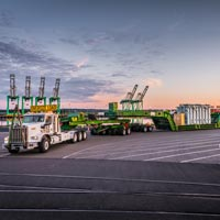 selected thumbnail button of An Omega Morgan 2015 Kenworth C500 and 150-ton trailer loaded with a shunt reactor ready for transport at dusk