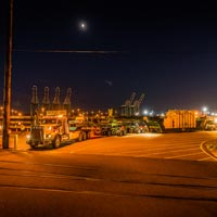 selected thumbnail button of an Omega Morgan 2015 Kenworth C500, 150-ton trailer, and push truck transporting a shunt reactor at night
