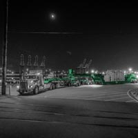 deselected thumbnail button of an Omega Morgan 2015 Kenworth C500, 150-ton trailer, and push truck transporting a shunt reactor at night