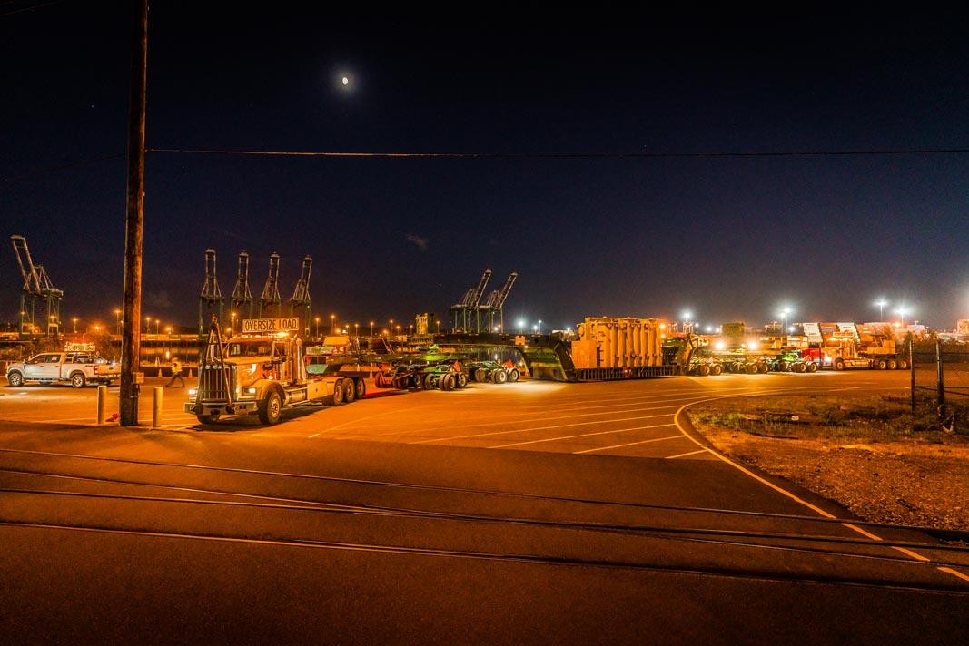 an Omega Morgan 2015 Kenworth C500, 150-ton trailer, and push truck transporting a shunt reactor at night