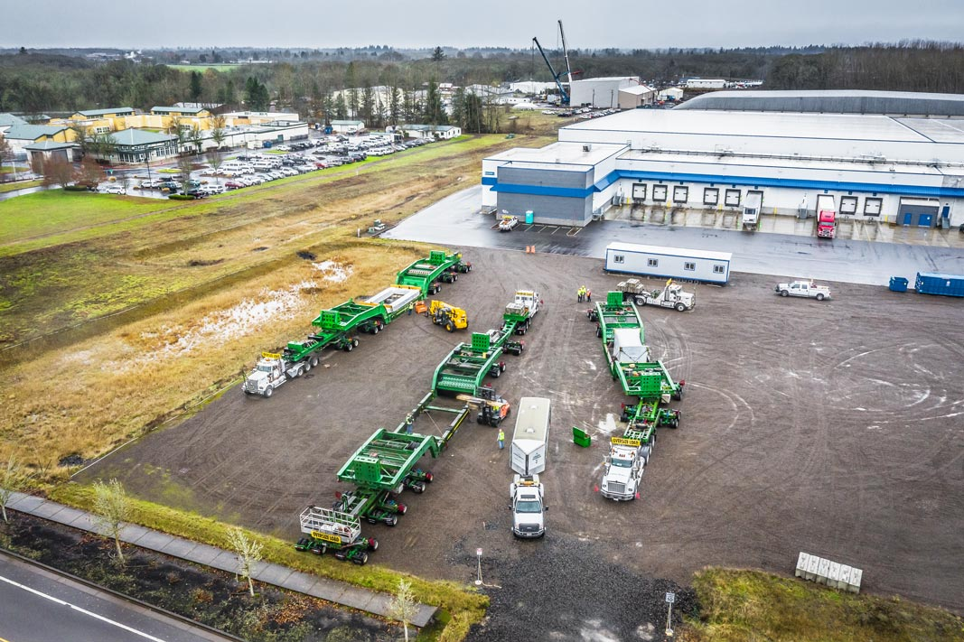 Omega Morgan's one hundred fifty ton dual lane transporter and one hundred sixty dual lane transporter parked near Stack Metallurgic's Albany facility where two Omega Morgan cranes are lifting the new hot isostatic press into a building