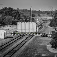 deselected thumbnail button of An Omega Morgan trailer transporting a large transformer across railroad tracks on its way to a barge