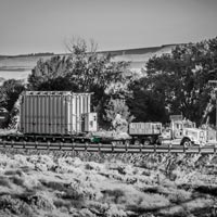 deselected thumbnail button of Omega Morgan specialized transportation convoy hauling a large transformer over a country road