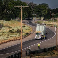 selected thumbnail button of Omega Morgan specialized transportation crew member stands on the side of the road to assist while a heavy transformer load comes up a winding road in Oregon state