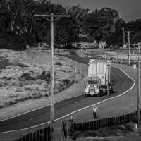 deselected thumbnail button of Omega Morgan specialized transportation crew member stands on the side of the road to assist while a heavy transformer load comes up a winding road in Oregon state